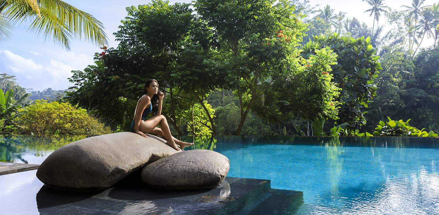 Young asian woman by a tropical pool setting.